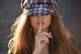 Chica joven con gorra y haciendo el gesto de silencio - 185730138