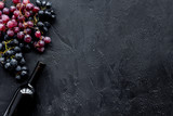 Wine bottle near bunches of red and black grapes on black background top view copyspace - 185747763