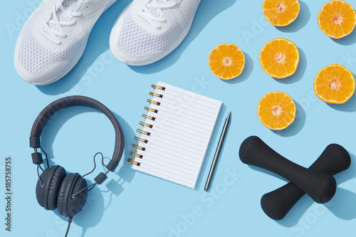 Female fitness flat lay, sneakers, dumbbells, notebook planner on blue background, healthy sports lifestyle New Year resolution - 185758755
