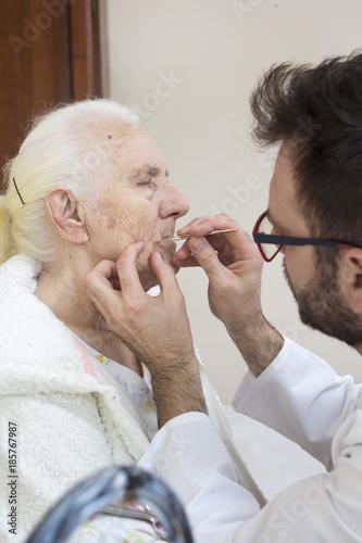 Zabiegi pielęgnacyjne na twarzy starej kobiety. Usuwanie włosów z twarzy pęsetą.