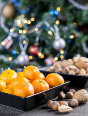 Mandarins and nuts in a bowl on the rustic table near a Christmas tree.