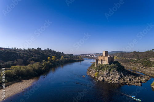 Aerial view of the Armourol Castle with a boat passing in the Tagus River in Por Poster
