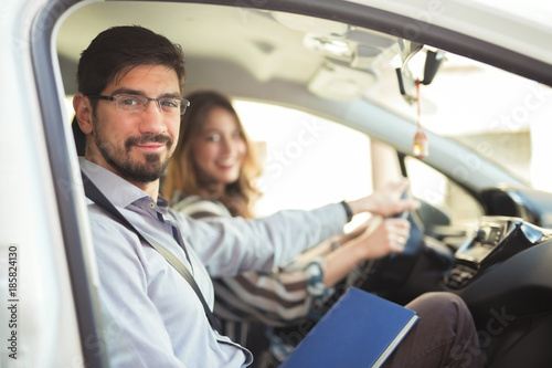Fototapeta Driving instructor is teaching his student how to drive a car