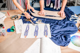 Cutting blue fabric on the table full of tailoring tools. Close-up view on the hands, fabric and fashion drawings - 185834732