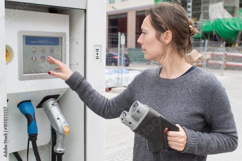 Leinwanddruck Bild Frau waehlt Ladevorgang fuer Elektoauto aus