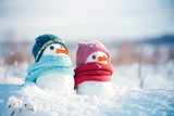 Two little snowmen the girl and the boy in knitted caps and scarfs on snow in the winter. Festive background with a lovely snowman. Christmas card, copy space - 185837954