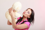 Childish young woman infantile girl in pink kissing teddy bear toy - 185845107