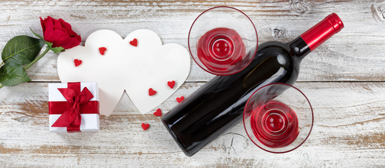 Valentines wine with gifts on rustic wooden background