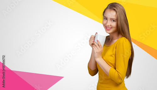 Casual young woman holding a cup of a hot drink in her hands