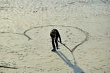 Des jeunes femmes dessinent des coeurs sur le sable d'une plage de Bretagne - 185883510