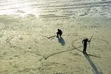 Des jeunes femmes dessinent des coeurs sur le sable d'une plage de Bretagne - 185883550