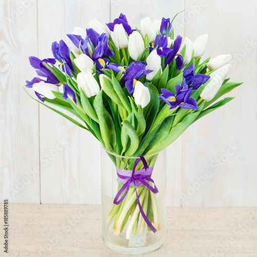 Fotobehang Iris bouquet of white tulips and blue irises on a wooden background