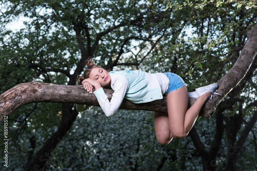 Wild fatigue. Beautiful young woman sleeping on a tree branch. Keeps his hands under his head
