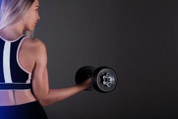 A sporty girl holds a dumbbell in her hands, shakes a muscular. Against a dark background © Natalya