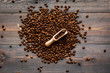Scattered coffee beans and beans in scoop on dark wooden table top view. Coffee background.
