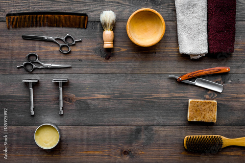 Vintage barbershop tools. Razor, sciccors, brush on dark wooden background top view pattern copyspace © 9dreamstudio