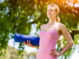 Young woman with a gym mat in the park - 185949366