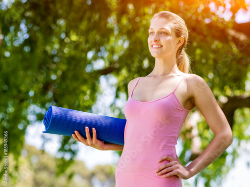 Wall mural Young woman with a gym mat in the park