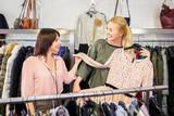 shop assistant helping chooses clothes - 185970772