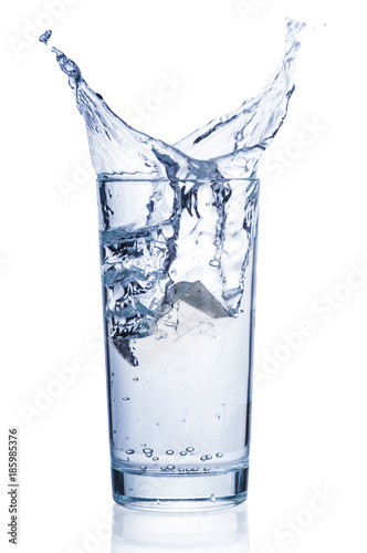 Pure water splashing out of tumbler on white background