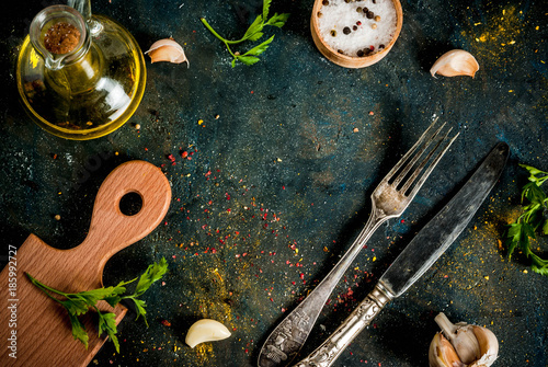 Cooking food concept, spices, herb and oil for preparing dinner, with cutting board, table knife and fork, copy space top view frame