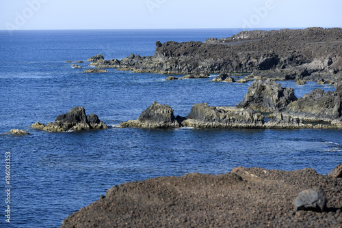 Deurstickers Grijs Volcanic rocks protruding from the assessment at the coast of the island of Lanzarote