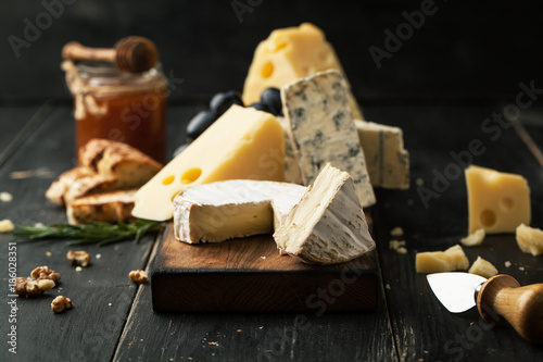 Fototapeta Assorted cheeses with grapes, nuts and rosemary