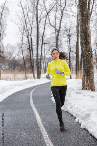 Winter runner girl training running in snow wearing cold weather clothes, gloves, warm yellow jacket. Asian woman jogging in park during snowfall. Active and fitness lifestyle.