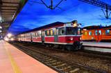 Pociągi stoją przy peronie na dworcu kolejowym.
