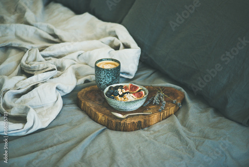 Healthy winter breakfast in bed. Rice coconut porridge with figs, berries and hazelnuts and cup of espresso over rustic wooden board background. Clean eating, alkiline diet, vegan food concept