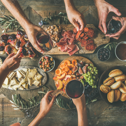 Flat-lay of friends hands eating and drinking together. Top view of people having party, celebrating together at vintage wooden rustic table set with different wine snacks and fingerfoods, square crop - 186057192