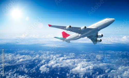 Fototapeta Airplane flying above clouds