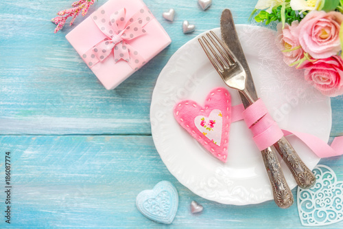 Romantic dinner concept. Table place setting with a white plate, vintage silverware tied with a pink ribbon and many different heart shape decorations, a gift and flowers