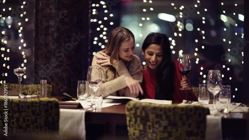 Two adolescent women going through the menue  in a fancy restaurant, while drinking a glass of red wine and laughing and talking, maybe gossiping