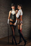 Portrait of steampunk girls in hat with glasses and cane in leather vest and stockings. - 186107939