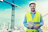 construction project engineer with blueprints at building site - 186114501