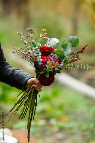 assembling a bouquet of roses dahlias and eucalyptus