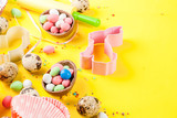 Sweet baking concept for Easter, cooking background with baking - with a rolling pin, whisk for whipping, cookie cutters, quail eggs, sugar sprinkling. Bright yellow background, top view copy space - 186114919