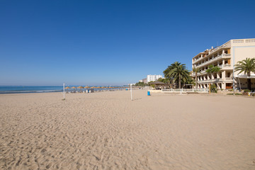 sandy and lonely Voramar Beach, in Benicassim, Castellon, Valencia, Spain, Europe. Buildings, blue clear sky and Mediterranean Sea. Horizontal