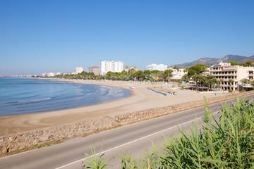 landscape sandy Voramar Beach, in Benicassim, Castellon, Valencia, Spain, Europe. Buildings, blue clear sky and Mediterranean Sea. Horizontal