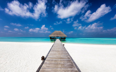 Tropischer Traumstrand mit Holzsteg zu einem Wasser Bungalow über türkisem Meer