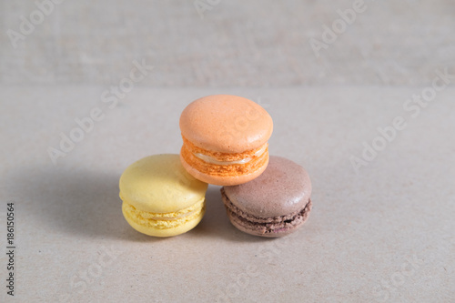 Fotobehang Macarons three colorful macarons cake lying on a gray sheet of paper abstraction