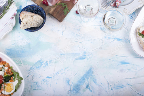 different food and a glass of wine on a white table - 186158160