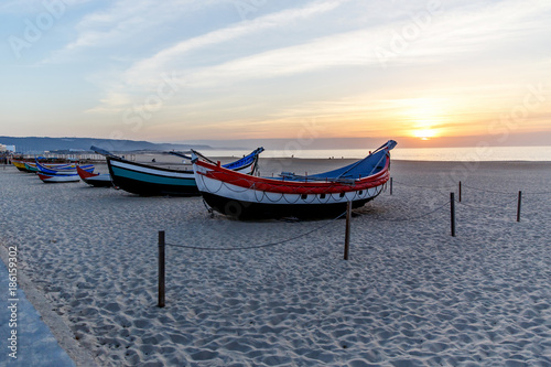 Fotobehang Koraalriffen fishing boat on the beach at sunset, Nazare, Portugal
