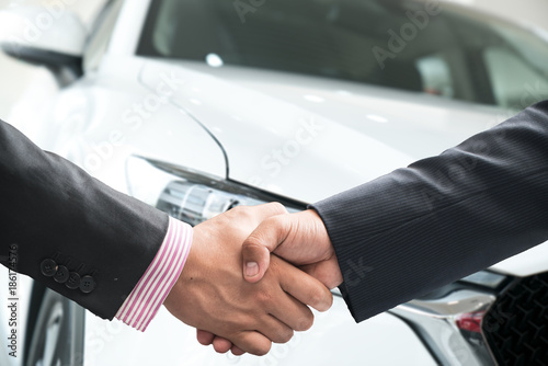 Close-up image of a firm handshake after a successful deal of buying a car.