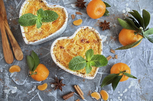 Baked cottage cheese pudding with cinnamon and tangerines on a grey stone, fresh tangerines and spices