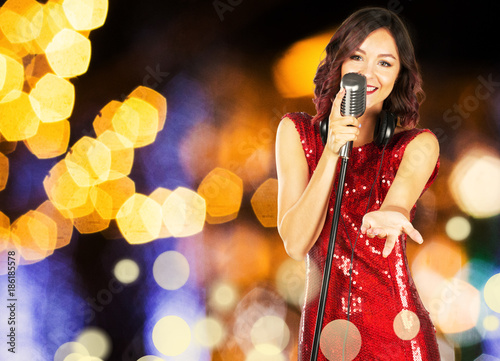 Beautiful and stylish woman singerwith a microphone - 186185578