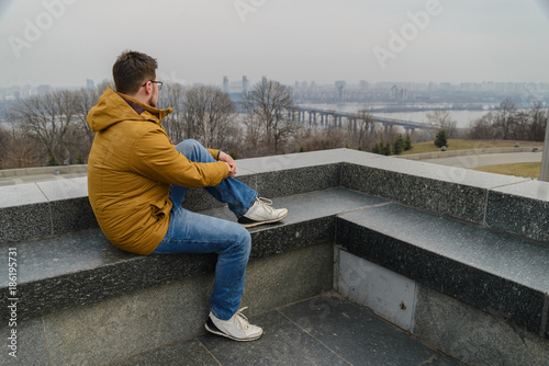 Foto op Plexiglas Kiev young man lookin at cityscape in cold autumn day