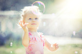 A little girl catches soap bubbles in summer park - 186198574