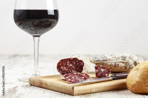 Salamino su tagliere con bicchiere di vino rosso